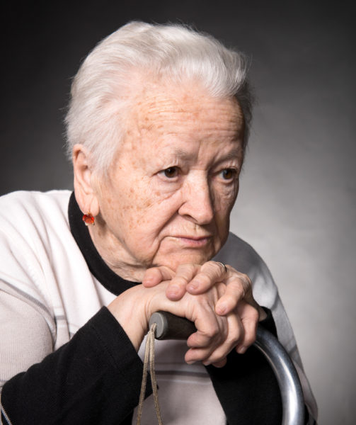 Portrait of old woman sitting with a cane