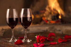 Two hands having a romantic toast in hotel room with flowers and fire behind